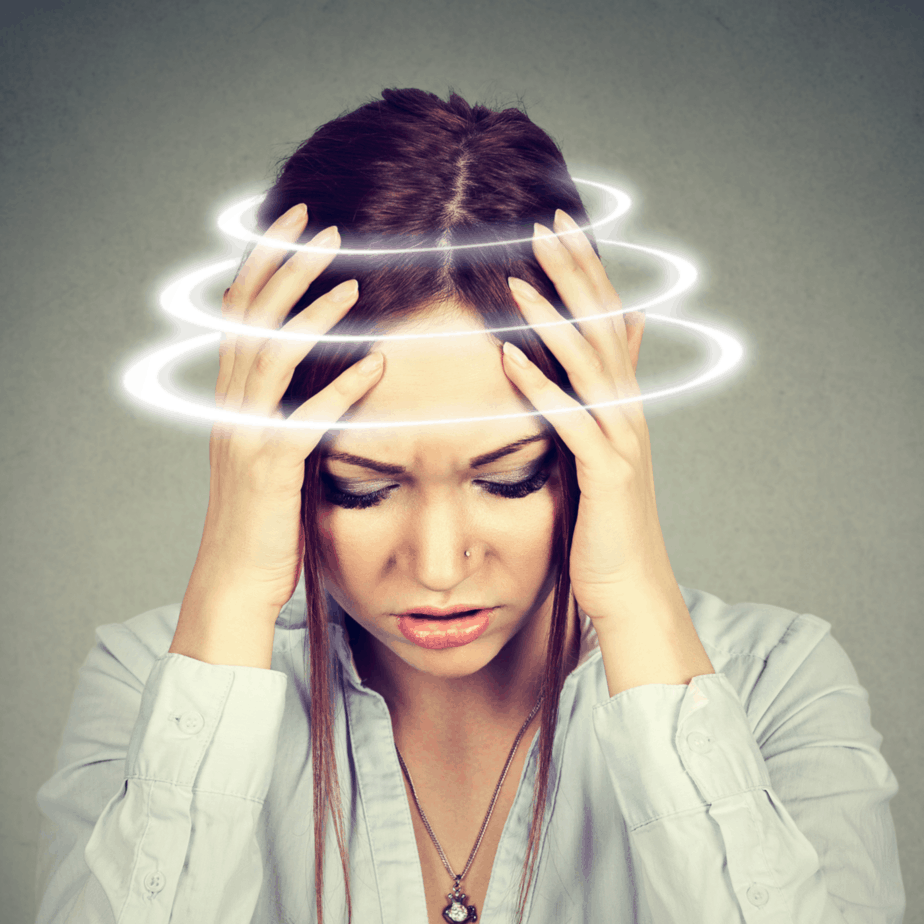 A woman holding her head because she is dizzy.